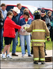 Volunteer Firefighter hands out candy during the 2015 Cremona Canada Day Parade. Photo by Brittney Pawson.